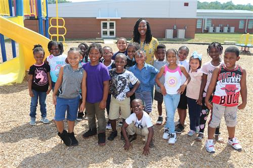 Ms.Thomas with her students at playground.