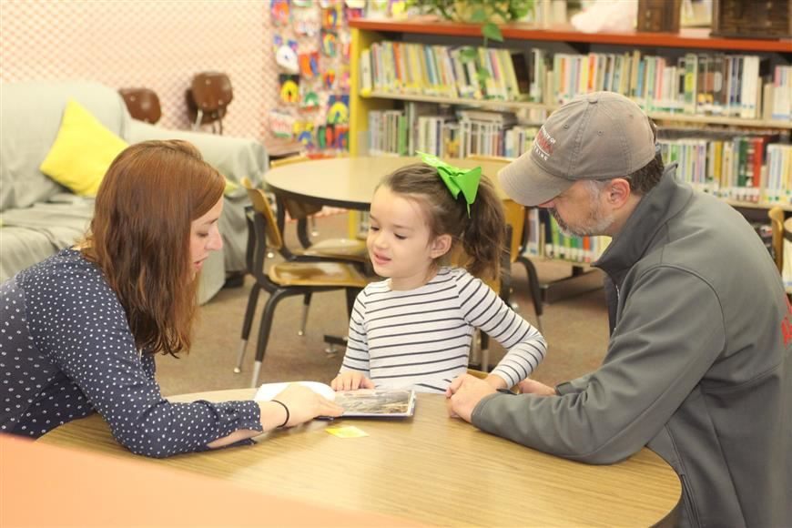 Child reading with adults