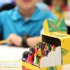Box of crayons on desk in classroom