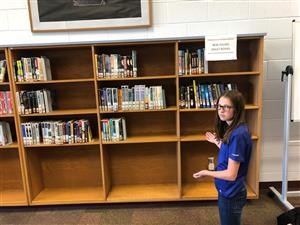 Student standing next to empty shelves